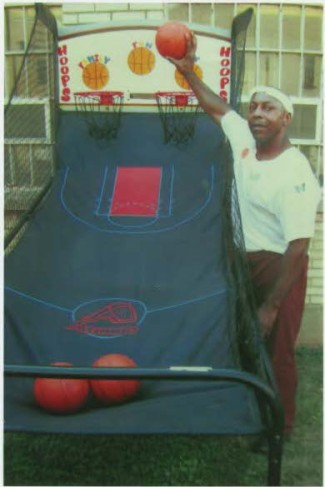 John holding a basketball in front of the backboard he painted for Family Fun Day, August 1 and 2, 2015.